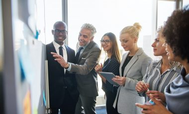 Smiling colleagues strategizing together on a whiteboard in an office